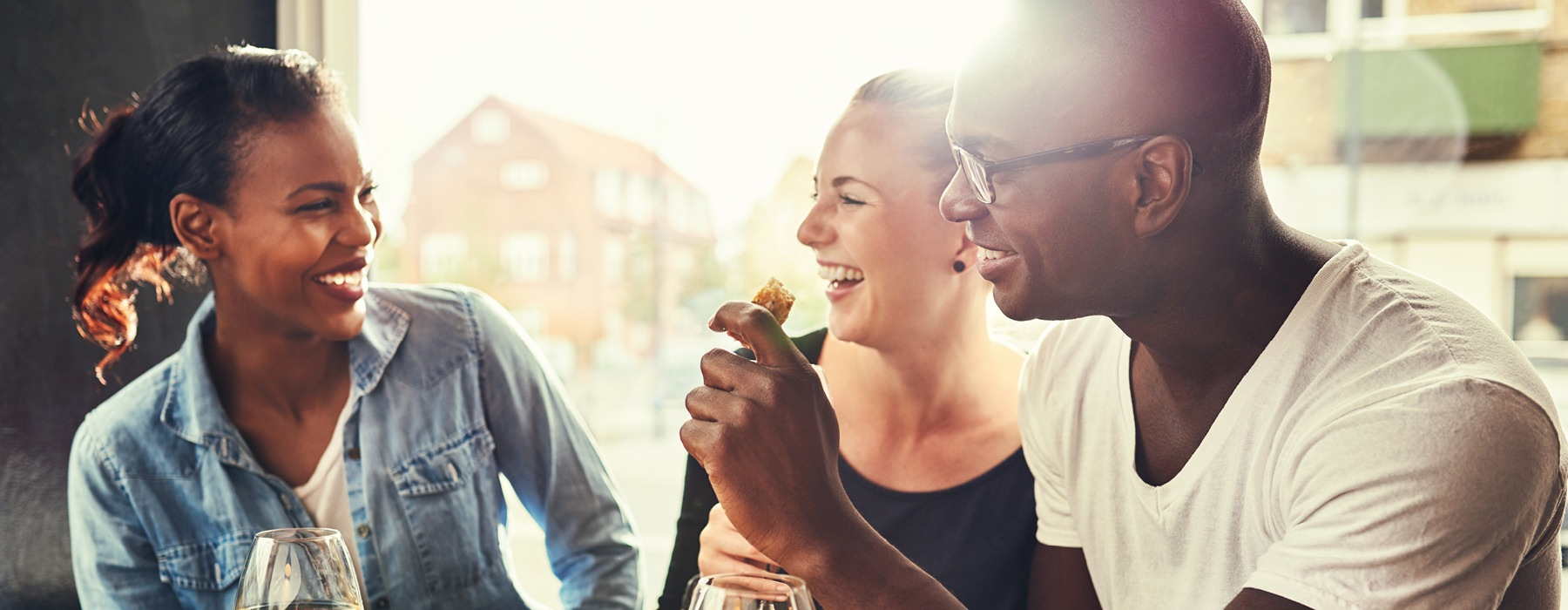 Man and two woman laughing while having a meal.